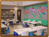 Room with tables and chairs out and construction paper flowers on the wall